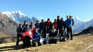 The drektrek team posing with Cornish flag with Everest behind, all wearing our poppies with pride